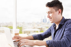 Young guy using laptop side Stock Photos
