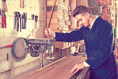 Young guy using machine to process plank Stock Photos