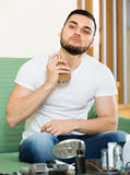 Young guy using perfume at home Stock Photography