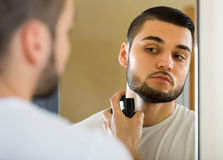 Young guy using perfume at home Royalty Free Stock Photo