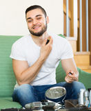 Young guy using perfume at home Stock Image