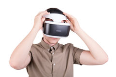A young guy in virtual reality helmet, isolated on a white background. Man action in virtual reality goggles. VR Glasses. royalty free stock images