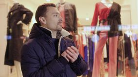Young guy waits someone standing in front of clothing shop. The man feels cold, rubs his hands and looking around. Prores codec stock footage