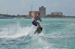 Young Guy Jumping While Wakeboarding in Aruba. Young guy wakeboarding and jumping off the coast of Aruba Royalty Free Stock Photo