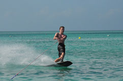 Young Guy Wakeboarding in the Tropical Blue Waters of Aruba. Young guy on a wakeboard in the tropical waters of Aruba Royalty Free Stock Photos