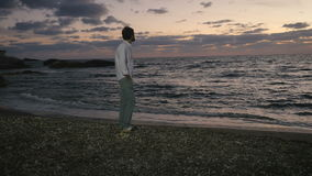 Young guy is walking on the beach and enjoys the evening seascape stock video footage
