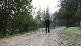 Young guy walks on a dirt road in the countryside in the mountains. And wood stock video footage