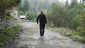 A young guy walks on a poor dirt road in the countryside in the mountains. Forest stock footage