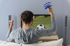 Young guy is watching football match Royalty Free Stock Photo