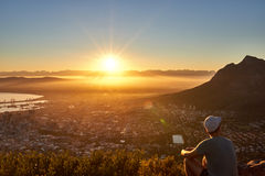 Young guy watching the sunrise over the city Royalty Free Stock Image