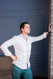 A young guy, wearing a white shirt with patterns, stands in a building and looks out the window Stock Images