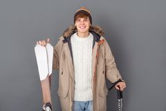 Young man studio on grey winter style standing with ski poles and skis close-up stock photography