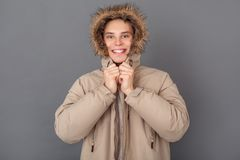 Young man studio isolated on grey winter style looking camera putting on hood royalty free stock photo