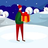 Young Guy in Winter Clothing Holding Present Box. royalty free stock photography
