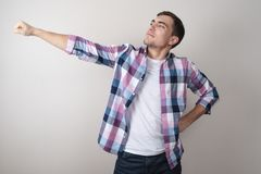 A young guy in a white t-shirt and a colored shirt posing as a superhero royalty free stock photos