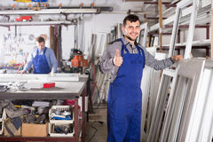 Young guy worker is inspecting the window frame. In workshop Royalty Free Stock Photo