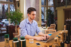 Young guy working on laptop in the Italian style kitchen Royalty Free Stock Photos