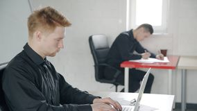Young guy is working with laptop sitting in workplace in modern office. Young guy is working with laptop sitting in workplace in modern office, employee doing stock video