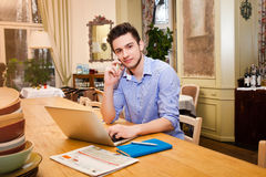 Young guy working on laptop and talking by phone in the Italian. Style kitchen Stock Photo