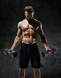 Young guy working out with dumbbells. Stock Image