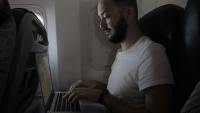 Young guy works with laptop while sitting on airplane.