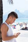 Young guy writing message with phone at beach Royalty Free Stock Photo