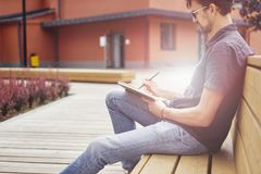Young guy writing in a note book sitting outside on wooden bench wearing glasses. Half-face portrait outside daylight or sanset.  Stock Images