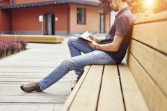 Young guy writing in a note book sitting outside on wooden bench wearing glasses. Half-face portrait outside daylight or sanset.  Royalty Free Stock Photos