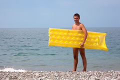 Young guy with yellow mattress on seacoast Stock Photography