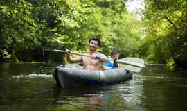 Young guys in boat with oars on river against background of green trees over water. Kayakers in kayak royalty free stock images
