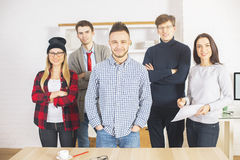 Young guys and girls in office. Front view of beautiful young european guys and girls in modern office with desktop. Teamwork concept stock photography