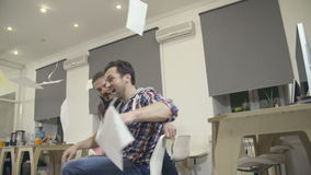 Young guys have fun in the office during a break stock video footage