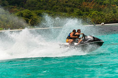 Young guys having fun in tropical water on jet ski. Beautiful tropical vacation in the warm sunny Seychelle island oceans and palm trees Stock Photography