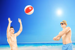 Young guys playing with a ball, next to a sea Stock Photos