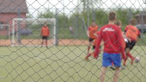 Young guys playing football in the stadium behind bars, background, copy space, slow motion, training. Young guys playing football in the stadium behind bars stock video footage