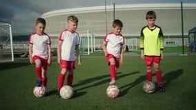 Young guys schoolchildren put balls on soccer field