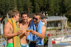 Young laughing guys in swimsuits drinking beer Royalty Free Stock Images