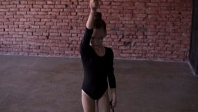 Young gymnast doing circle with mace on the legs in the studio on window and brick wall on the background. Slow motion. Footage stock video footage