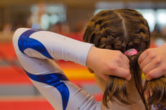 Young gymnast girl fixing hair before appearance Stock Images