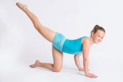 Young gymnast girl in leg stretch pose Stock Photos