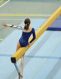 Young gymnast girl performing routine on balance beam Stock Images