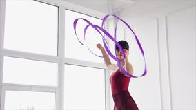 A young gymnast is trained to dance with a ribbon that flutters in the air. A young gymnast performs dance elements with a ribbon, a lady performs a stock footage