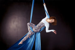 Young gymnast training on aerial silk. Young gymnast doing exercise on aerial silk Royalty Free Stock Photography
