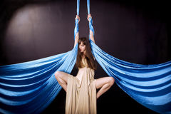 Young gymnast training on aerial silk. Young gymnast training flexibility on aerial silk Royalty Free Stock Image