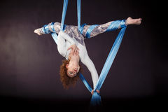 Young gymnast training on aerial silk. Young gymnast training handstand on aerial silk Stock Photos