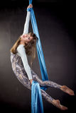 Young gymnast training on aerial silk. Young gymnast training strength on aerial silk Stock Photo