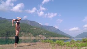 Young gymnasts are training in Turkey on vacation. Against the backdrop of the Turkish mountains, the guys athletes perform different tricks stock video footage