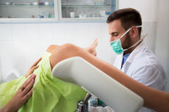 Young gynecologist exam his patient at clinic. Young professional gynecologist exam his patient at clinic Stock Images