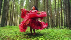 A young gypsy beauty in bright barefoot dress whirls dancing in the forest.