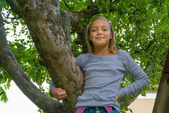 Young gypsy child on tree smiling Stock Photography